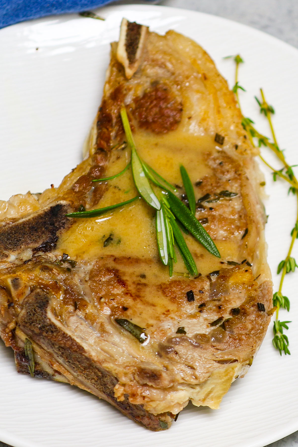 These Veal Chops are quick and easy to make, with a taste that's better than a Michelin star restaurant. Bone-in veal chops are marinated with fresh rosemary, thyme, salt, and pepper, then tenderized to succulent perfection! Drizzle them with homemade rosemary butter sauce for the most delicious dinner!